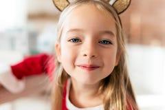 För dräktren för gullig ung flicka bärande horn på kronhjort och att le och se kameran Lycklig unge på jul royaltyfria bilder