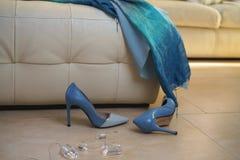 För dräktsamling för parti kvinnliga smycken för tillbehör för skor för klänning för blått på den beigea soffan på golv i inre Ef arkivbilder