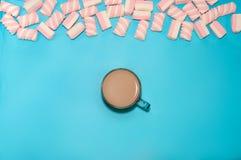För drinkkakao för jul mjölkar varm kaffe eller choklad med kräm och marshmallower i en liten genomskinlig kopp på en blå bakgrun Royaltyfri Foto