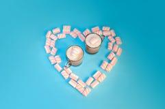För drinkkakao för jul mjölkar varm kaffe eller choklad med kräm och marshmallower i en liten genomskinlig kopp på en blå bakgrun Fotografering för Bildbyråer