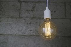 För Edison för tappning glödande kula typ på den gråa väggen royaltyfri fotografi