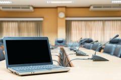 För en konferens - bärbar dator framme av tomma stolar på confere Royaltyfria Bilder