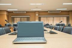 För en konferens bärbar dator framme av tomma stolar på conferenc Royaltyfria Foton