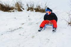 För en pulka ner pojken i röda flåsanden är jätteglat fotografering för bildbyråer