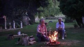 För en romantisk afton runt om lägerelden behöver du också en bra bränningbrand arkivfilmer