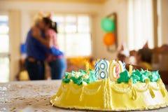 För födelsedagparti för beröm som 80 dotter kramar den gamla fadern royaltyfri fotografi