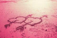 För förälskelsehjärta för rosa färger två tecken med attraktion för kupidonpilhand på stranden Arkivbild