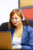 För för kontorskläder och hörlurar med mikrofon för ung attraktiv kvinna bärande sammanträde av skrivbordet som ser datorskärmen  Arkivfoton