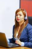 För för kontorskläder och hörlurar med mikrofon för ung attraktiv kvinna bärande sammanträde av skrivbordet som ser datorskärmen  Royaltyfri Fotografi