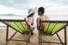 För familjlopp för par lyxig avkoppling på den tropiska stranden för stol Royaltyfri Bild