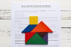 För fastighetköp för bästa sikt kontakt med tangramen som formas som hus royaltyfria bilder