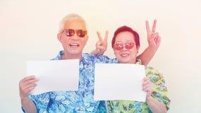 För ferieskjorta för höga asiatiska par bärande tra för tecken hållande vit Arkivfoto