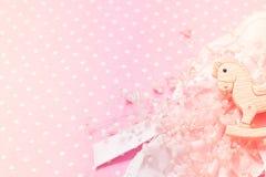 För filtbakgrund för flickan snör åt pryder med pärlor det rosa partiet för baby shower med den lilla vagga ponnyleksaken, och de arkivbild