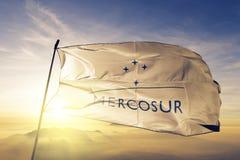 För flaggatextil för Mercosur som Mercado Comun del Sur tyg för torkduk vinkar på den bästa soluppgångmistdimman stock illustrationer