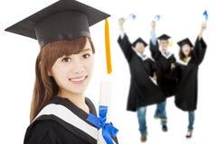 För flickastudent för ung kandidat hållande diplom med klasskompisar royaltyfria bilder