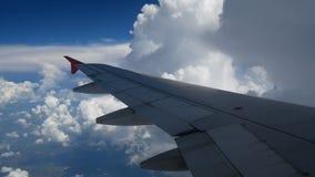 för flygplanlandning för längd i fot räknat 4K flyg vinge av ett flygplan som in flyger till de vita molnen och den blåa himlen arkivfilmer