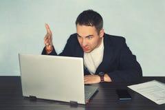 För freelancerprogrammerare för ung man användaren för PC med ett missnöjt bittert ilsket uttryck på hans framsida som framme ser royaltyfri bild