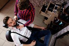 För frisörsnitt för professionell ledar- skägg för klient arkivbild