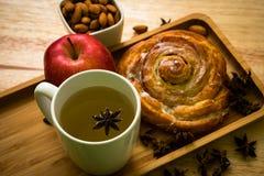 För för frukostäpple och te för kanelbrun rulle träbackgroud arkivfoton