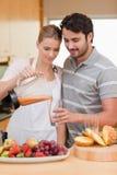 för fruktfruktsaft för par dricka stående Fotografering för Bildbyråer