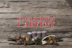 För garneringadvent för glad jul undersöker brinnande grå färger suddig tysk 1st för bakgrundstextmeddelandet Arkivfoto
