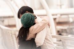 För garnhatt för asiatisk lycklig kvinna bärande möte och krama med boyfrie Royaltyfri Fotografi