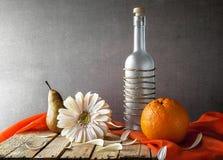 För gerberaflaska för stilleben vita frukter Arkivfoto