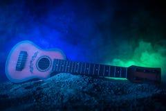 för gitarrillustration för begrepp elektrisk musik Akustisk gitarr som isoleras på en mörk bakgrund under stråle av ljus med rök  royaltyfria foton