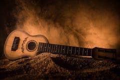 för gitarrillustration för begrepp elektrisk musik Akustisk gitarr som isoleras på en mörk bakgrund under stråle av ljus med rök  royaltyfri bild