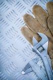 För glidbanaklämma för skyddande handskar skruvnyckel för apa på kanaliserad meta arkivbild