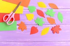 För gräsplan, röda och orange för snitt papperssidor för guling, sax, färgat papper täcker på lila träbakgrund closeup Royaltyfria Foton