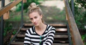 För grov bomullstvillomslaget för den lyckliga stilfulla flickan parkerar bärande sammanträde på trätrappa i en stad Royaltyfria Bilder