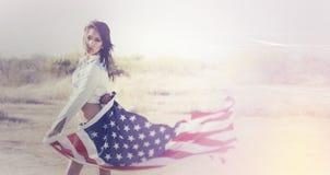 För grov bomullstvillskjorta för kvinna bärande hållande amerikanska flaggan Arkivbilder