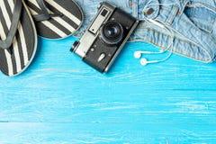 För häftklammermatarejeans för ram eleganta kvinnliga hörlurar för kamera på blå träbakgrund, copyspace för text, sommarsemester royaltyfri bild