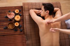 För häleribaksida för ung man massage i brunnsort royaltyfri bild