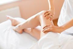 För häleriben för ung kvinna massage på den Spa mitten kvinna för vatten för brunnsort för hälsa för huvuddelomsorgsfot royaltyfri bild