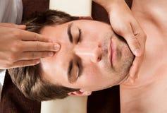 För häleripanna för ung man massage i Spa arkivfoton