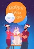 För hälsningkort för lyckligt nytt år man och kvinna i Santa Hats Embracing Dog Symbol av 2018 Arkivbild