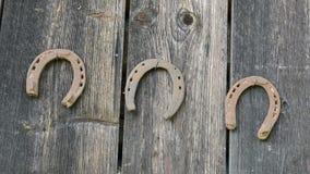 För hästsko för tappning som rostig flyttning hänger den gamla trähusväggen lager videofilmer