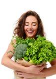 För hålllivsmedelsbutik för ung kvinna påse för shopping för papper mycket av nya gröna grönsaker royaltyfria bilder