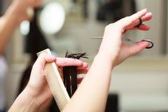För hårkvinna för frisör bitande klient i friseringskönhetsalong Arkivfoton