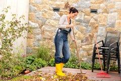För höstsidor för ung kvinna svepande veranda fotografering för bildbyråer