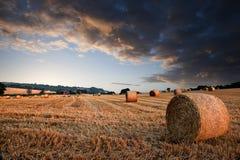 för hötimme för baler härlig guld- solnedgång för liggande Arkivfoto