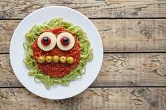 För halloween för grön spagettipasta idérikt spöklikt monster mat med leendetomatsås och roliga stora mozzarellaögonglober Royaltyfri Foto