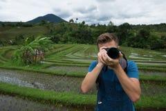 För handelsresandedanande för ung man som fotoet och att koppla av var utomhus- på risfält terrasserade på, i Bali Indonesien Arkivbild