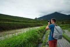 För handelsresandedanande för ung man som fotoet och att koppla av var utomhus- på risfält terrasserade på, i Bali Indonesien Fotografering för Bildbyråer