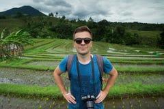 För handelsresandedanande för ung man som fotoet och att koppla av var utomhus- på risfält terrasserade på, i Bali Indonesien Royaltyfri Foto