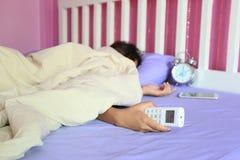 För handhåll för ung kvinna avlägsen luftkonditioneringsapparat och sova i arkivbild