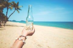 För handinnehav för unga kvinnor flaska med snäckskalet på den tropiska stranden i sommar Royaltyfri Bild