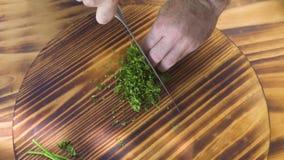 För handkock för bästa sikt som kock klipper grön persilja på träbräde Kockkock som hugger av ny persilja på skärbräda lager videofilmer